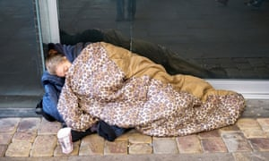 A homeless woman sleeps rough on Market St. Manchester, UK.