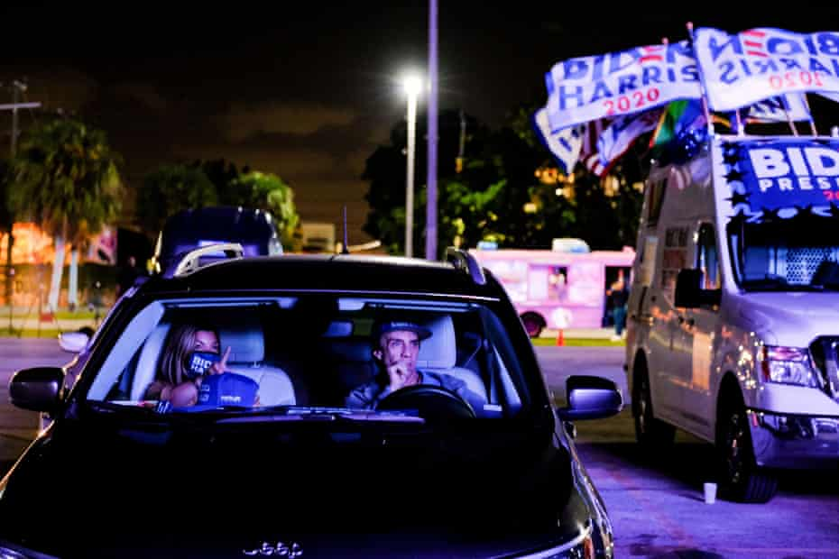 Biden supporters watch the screen as another poll closes, during a drive-in watch party at Mana Wynwood Convention Center during the 2020 U.S. presidential election in Miami, Florida