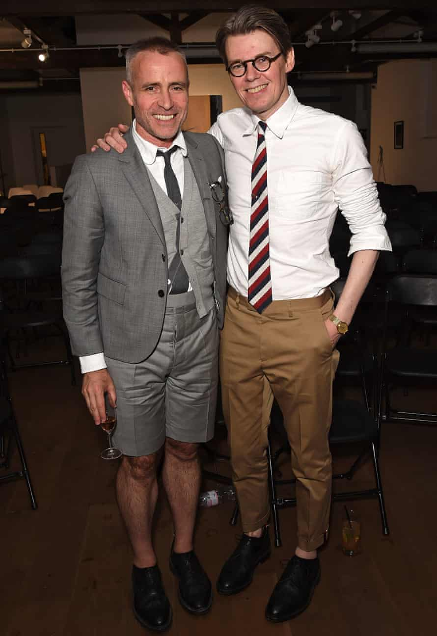 Andrew Bolton in ankle-length trousers, a white shirt and tie, with Thom Browne in a grey suit with knee-length trousers