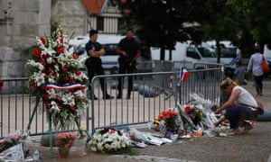 A woman lights a candle in front of the Saint-Etienne du Rouvray church where priest Jacques Hamel was killed.
