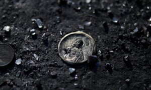 A charm depicting Jesus Christ is seen in the ashes of a house in Mati