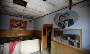 A wedding picture and a poster with the image of China's late Chairman Mao Zedong are seen on a wall inside a damaged room of Zhang Chungou's house in Shiyanzhuang village of Datong.