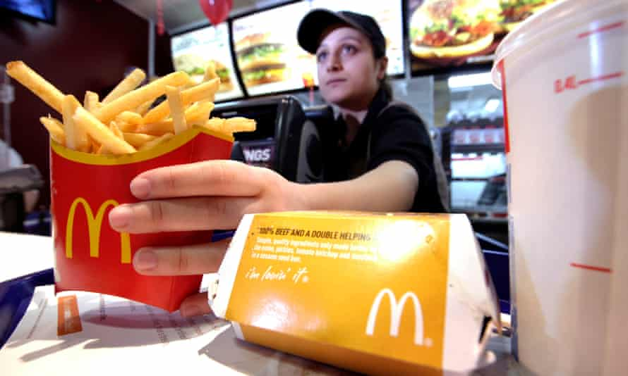 A McDonald's worker serves a burger and a carton of french fries in London
