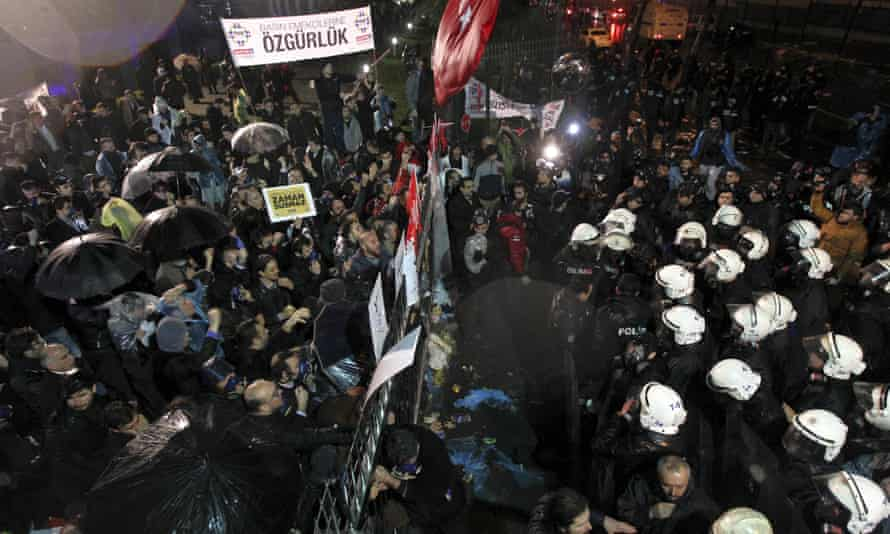 Riot police in white helmets try to enter the Zaman's HQ