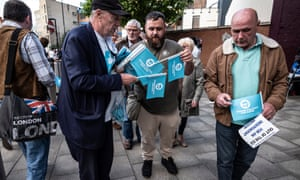 Brexit party campaigners hand out flags at its London rally.
