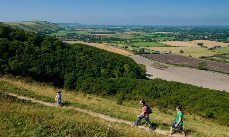 A family walks along the top of the South Downs escarpment in Sussex.