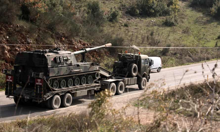 A Turkish army truck loaded with a tank heads to the Syrian border near Yayladagi, Turkey.