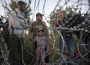 <strong>Roszke, Hungary</strong> Syrian refugees wait at the barbed wire fence, on the border between Hungary from Serbia. Hungary deployed police reinforcements to rein in an unrelenting flow of migrants across its porous border, but refugee activists said the effort appeared futile in a nation whose migrant camps are overloaded and barely delay their journeys west into the heart of the European Union.