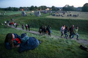 People make their way up the bank to watch the sun rise at the Avebury stone circle in Wiltshire
