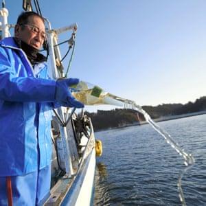 Fisherman Shozaburo Abe, 66, pours sake in the sea to commemorate his elder brother Katsuji