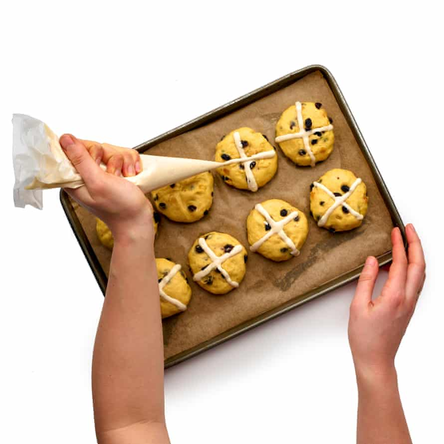Form the buns, score crosses on top and pipe flour paste into the crosses.
