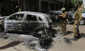 Soldiers take notes on a car that was burnt out outside the Splendid Hotel in Ouagadougou, Burkina Faso.