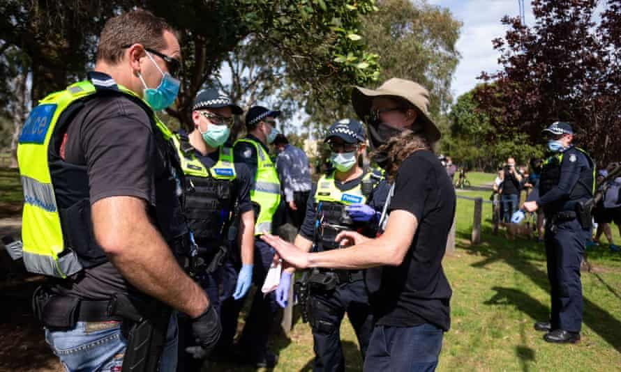 A protester is questioned during a freedom protest in Melbourne, held in response to the government's Covid-19 restrictions.