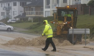 A loader moves tons of sand pushed by strong winds and rain onto a coastal road in Sydney's beachside suburb of Cronulla. REUTERS/Jason Reed