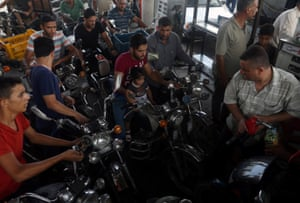Palestinians wait at a petrol station in the southern Gaza Strip to fill containers with fuel