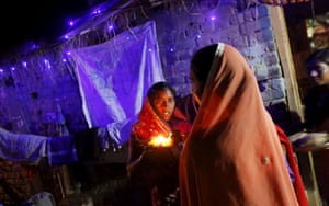 Female followers of Ramnami Samaj welcome the priests and elders of their religious movement as they arrive to attend a prayer meet at a house in the village of Chandlidi