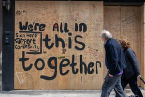 'We're all in this together' painted on to a boarded-up bar in New York City