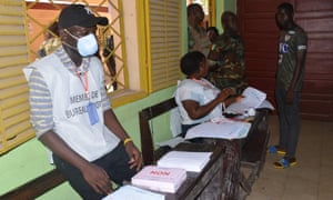An electoral official wears a face mask at a polling station in Conakry