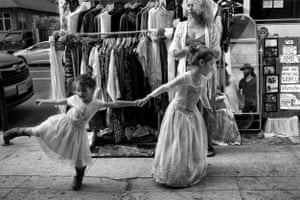 Six-year-old Flor drags her three-year-old sister Lua by the hand as they play in front of their parents' improvised vintage clothing display on Venice's popular Abbot Kinney Boulevard