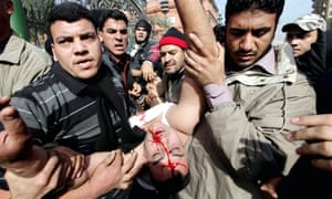 Egyptian protesters carry an injured officer as pro- and anti-Mubarak protesters clash in Cairo in February 2011.
