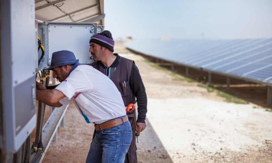 Men work on power junction box in solar field