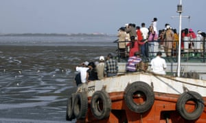 People watch flamingos from a boat during the Bombay Natural History Society's flamingo festival.