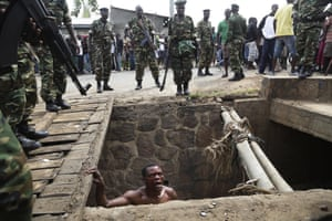 A suspected member of the ruling party's Imbonerakure youth militia pleads with soldiers to protect him
