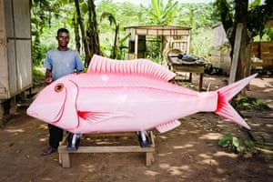 """Accra, Ghana. Longitude: -0¡ 52' 22.17"""" A fantasy coffin in the shape of a fish with its creator in a workshop in Pokoasi Town, Ga district. The made-to-order coffins, which pay tribute to the deceased with a personalised design, are recognised as an art form. Examples have been exhibited around the world"""