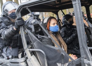 A climate activist is escorted from a forest after her arrest in Niederklein, Germany