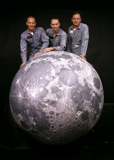 buzz aldrin michael collins and neil armstrong pose for a press shot with a large model of the moon