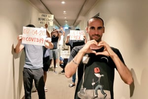 Moz Azimi in a corridor of a hotel with refugees holding signs