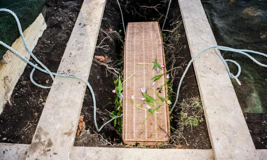 A wicker coffin is lowered into a grave