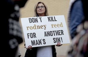 A woman holds a sign during a protest against the execution of Rodney Reed on 13 November 2019, in Bastrop, Texas.