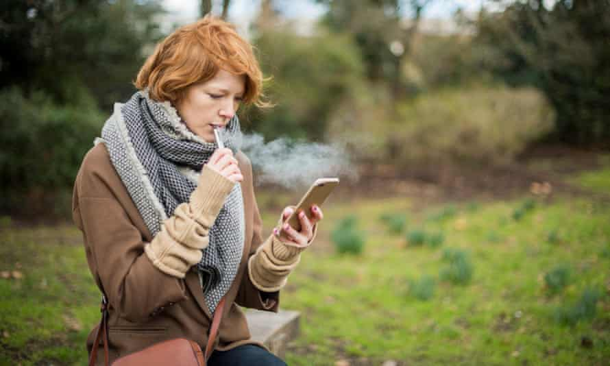 A young woman vapes while she checks her phone.