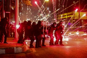 Fireworks thrown by anti-government protesters explode in front of a line of riot police in Bangkok, Thailand