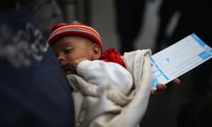 A mother holds her baby and a train ticket as they wait to board a train at Keleti station in central Budapest to take them to the Austrian border.