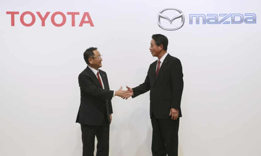 Toyota president Akio Toyoda and Mazda president Masamichi Kogai shake hands after announcing a plan to spend $1.6bn on auto manufacturing in the US.