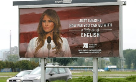 Cars drive behind a billboard in Zagreb promoting English-language courses with a photo of Melania Trump.