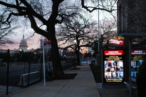 A wanted poster (R) by the FBI is displayed at a bus stop in the now-fenced Independence avenue southwest near the US Capitol (L), as security perimeters expand ahead of the inauguration in Washington, DC, USA, 18 January 2021. The FBI is seeking the public's help in identifying the insurrectionists that stormed the US Capitol as the Congress worked to certify the electoral votes for the Presidential election.