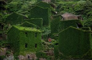 Shengshan, China A villager walks between abandoned houses