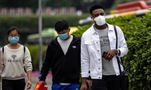 An African man and two Chinese people in face masks in Guangzhou