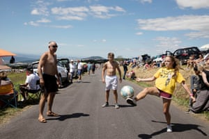 Spectators play football as they wait for the tour to pass through near Col de Peyra Taillade