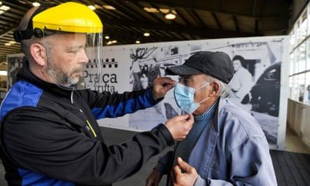 A man is given a face mask at a fruit market in Caldas da Rainha, Portugal.