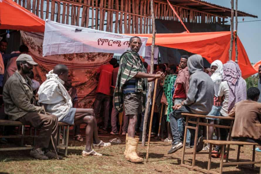 Villagers wait to vote outside a polling station.