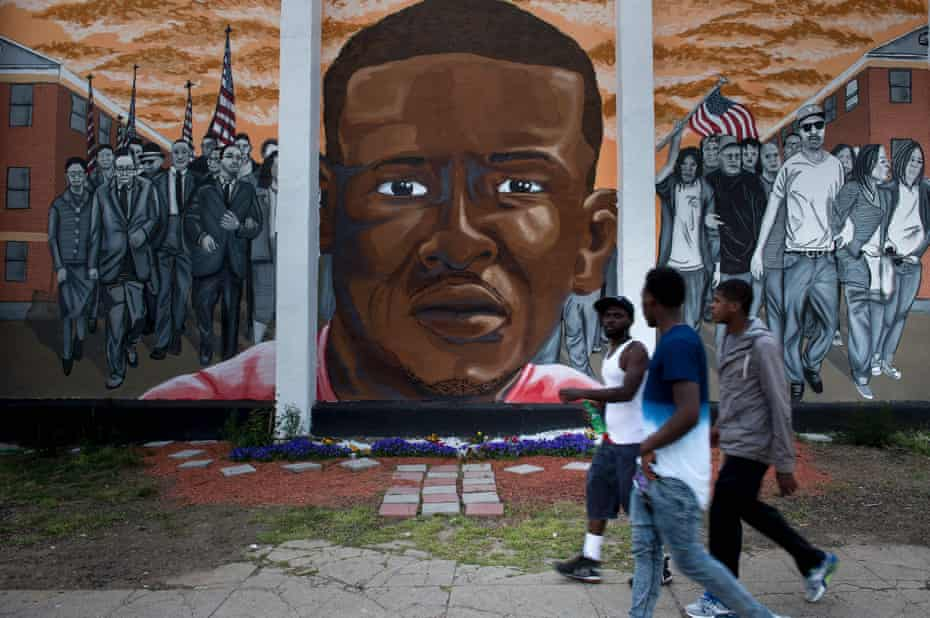 People pass a mural depicting Freddie Gray a year after the protests that were sparked by Gray's death in police custody. Baltimore agreed to a $6.4m settlement with the family.