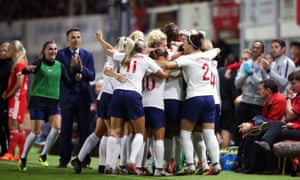 Phil Neville look on as the England players celebrate.