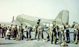 Black paratroopers prepare for a flight in an undated photo.