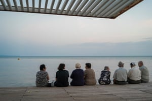 A group of eight people sit, on the promenade, in Durres, Albania, and look out at the sea.  The city was, briefly, renamed Durrës-Enver Hoxha during the late 80s, then (after the fall of communism) it became the location for mass migrations to Italy. In the past couple of decades, Durrës has undergone a facelift.