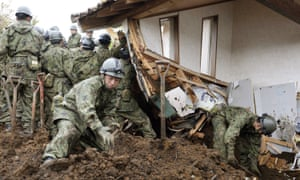 Members of Japan's Self-Defence Force search on Monday for missing people after a landslide in Minamiaso.