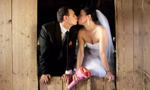 A bride and groom kissing in a barn
